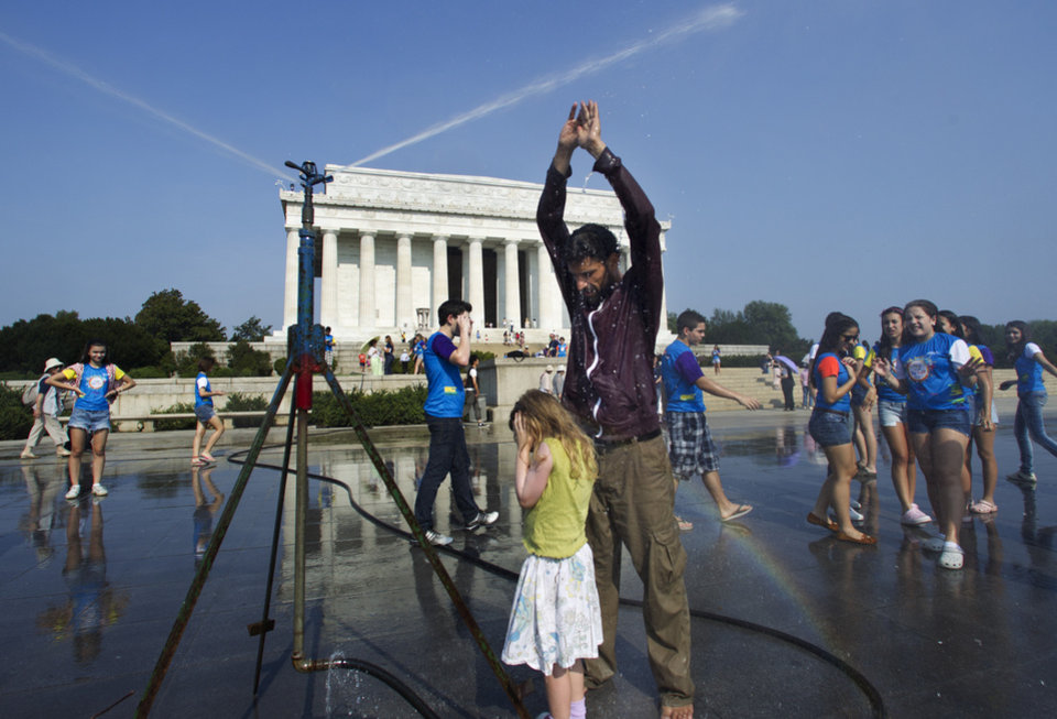 Photo -   Visitors get much needed relief from a water sprinkler set up at the National Mall near the Lincoln Memorial, rear, in Washington Saturday, July 7, 2012. The heat gripping much of the country is set to peak Saturday in many places, including some Northeast cities, where temperatures close to or surpassing 100 degrees are expected. (AP Photo/Manuel Balce Ceneta)