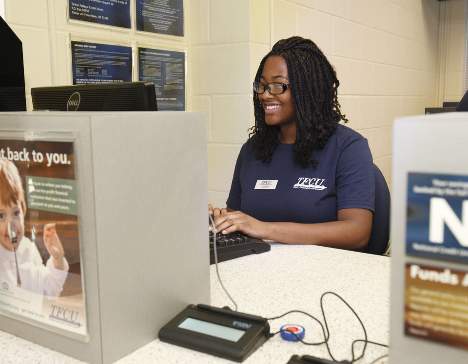Photo - John Marshall High School student Alexis Carney works in the teller window after the opening of a Tinker Federal Credit Union branch at the school. Photo by Paul Hellstern, The Oklahoman  PAUL HELLSTERN - Oklahoman