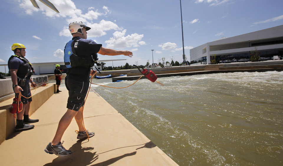 Photo -  Maj. Brad Smith throws a rescue line as Oklahoma City Fire Station 8 practices swift-water rescue techniques at Riversport Rapids.