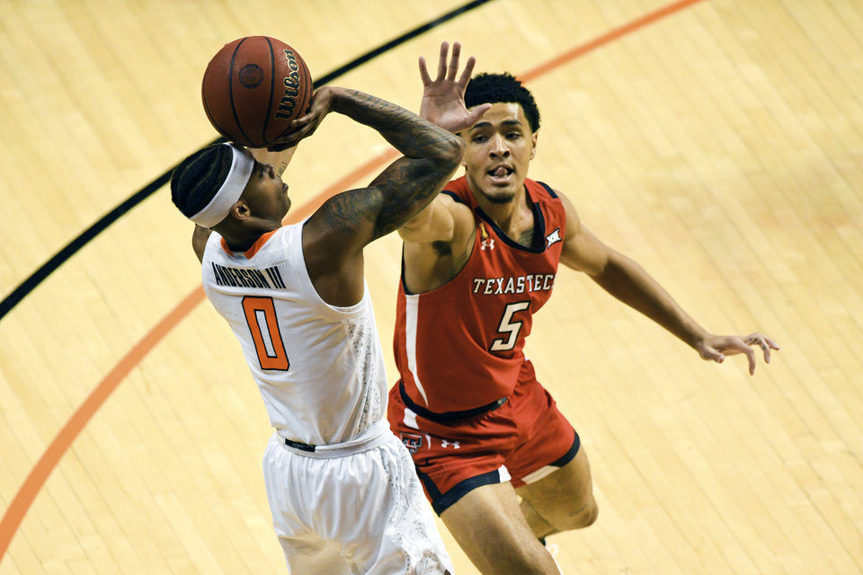 Photo - Texas Tech guard Micah Peavy (5) attempts to block the shot of Oklahoma State guard Avery Anderson III (0) during an NCAA college basketball game Monday, Feb. 22, 2021, in Stillwater, Okla. (AP Photo/Brody Schmidt)