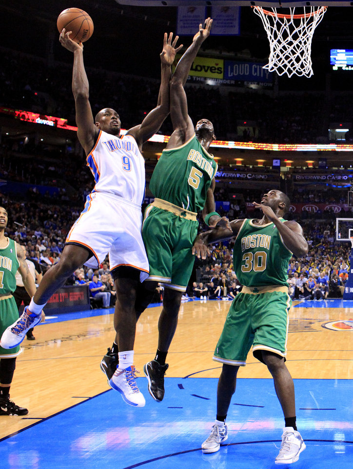 Oklahoma City's Serge Ibaka (9) shoots a lay up as Boston's Kevin Garnett (5) and Boston's Brandon Bass (30) defend during the NBA game between the Oklahoma City Thunder and the Boston Celtics at the Chesapeake Energy Arena in Oklahoma City, Sunday, March 10, 2013. Photo by Sarah Phipps, The Oklahoman