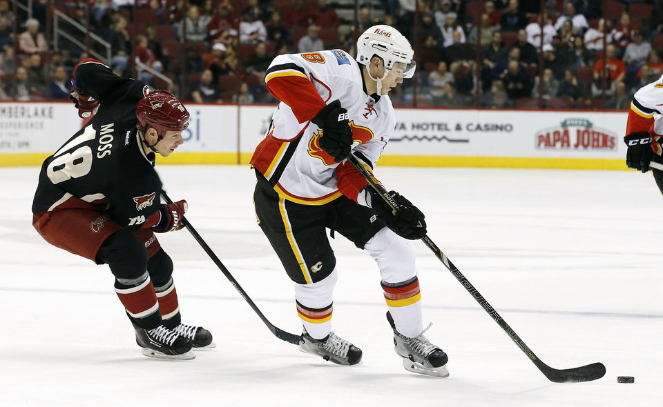 Photo - Calgary Flames' Joe Colborne (8) skates with the puck in front of Phoenix Coyotes' David Moss (18) during the first period of an NHL hockey game, Tuesday, Jan. 7, 2014, in Glendale, Ariz. (AP Photo/Ross D. Franklin)