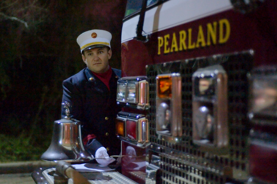 A member of the Pearland Fire Department rings the bell 26 times during a vigil in Pearland, Texas Friday, Dec. 21, 2012.   (AP Photo/The Courier, Kirk Sides)