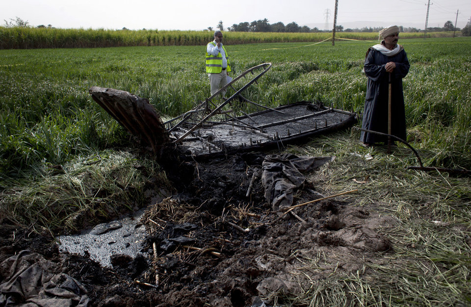 An Egyptian inspector of the Civil Aviation Authority, left, works at the site of the balloon accident, in Luxor, Egypt, Tuesday, Feb. 26, 2013. A hot air balloon flying over Egypt's ancient city of Luxor caught fire and crashed into a sugar cane field on Tuesday, killing at least 19 foreign tourists in one of the world's deadliest ballooning accidents and handing a new blow to Egypt's ailing tourism industry. (AP Photo/Nasser Nasser)