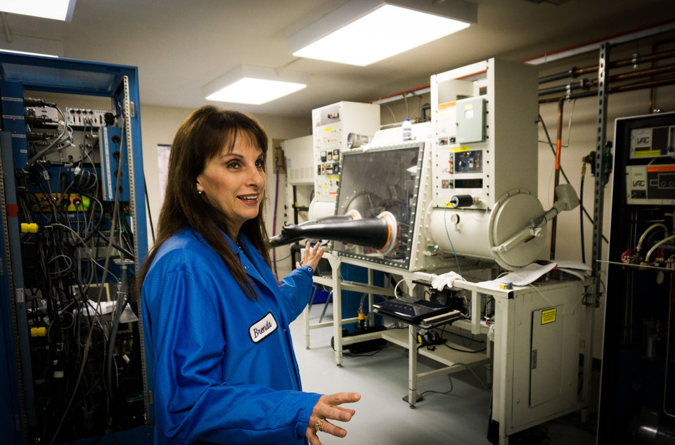 Photo -  Frontier Electronics Systems CEO Brenda Rolls discusses some of the specialized equipment her company uses to develop, test and manufacture nanotechnology. [Photos provided]