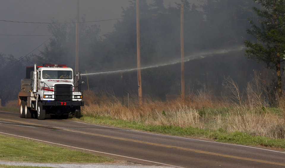 Photo - A truck sprays water into brush along Seward Rd. near Pine during wildfires in Logan County, Sunday, May 4, 2014. Photo by Nate Billings, The Oklahoman