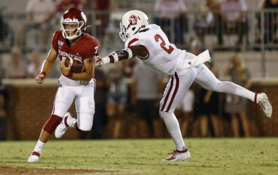 Photo -  Oklahoma's Spencer Rattler, left, runs through an arm tackle by South Dakota's Mike Johnson during the Sooners' win Sept. 7 in Norman. [Nate Billings/The Oklahoman]