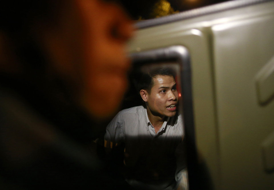 Photo - Apichat Pongsawat, a Thai activist, sits in a soldier vehicle after he was detained by soldiers while staging a protest against the coup in downtown Bangkok, Thailand Friday, May 23, 2014. Ousted members of Thailand's former government turned themselves in to the country's new military junta Friday, as soldiers forcefully dispersed hundreds of anti-coup activists who defied a ban on large-scale gatherings to protest the army's seizure of power. (AP Photo/Wason Wanichakorn)