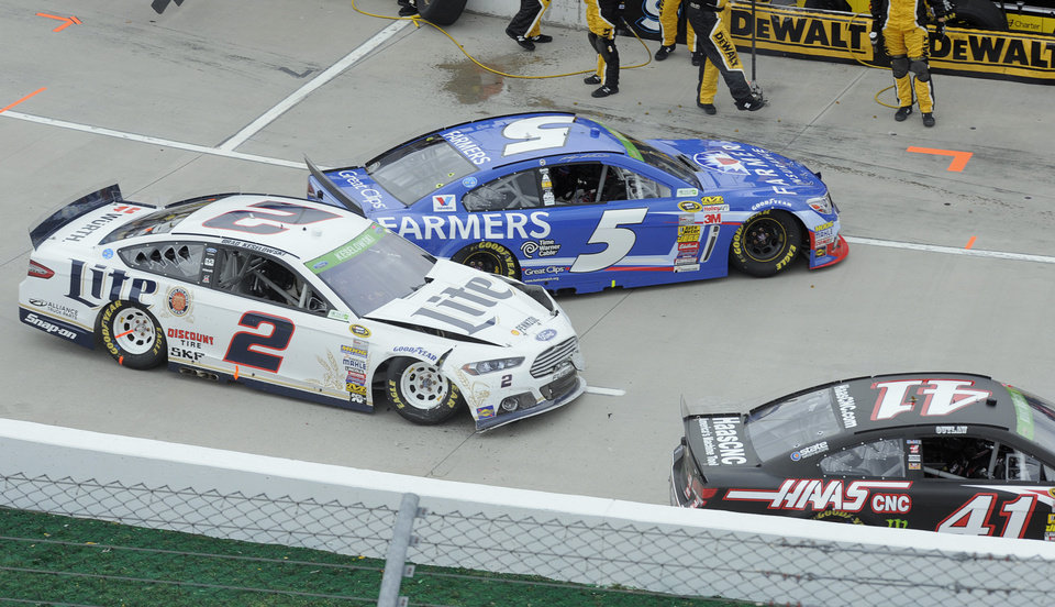 Photo - Brad Keselowski's (2) car is damaged in a pit road accident with Kasey Kahan (5) and Kurt Busch (41) during a NASCAR Sprint Cup Series auto race at Martinsville Speedway in Martinsville, Va., Sunday, March 30, 2014. (AP Photo/Mike McCarn)