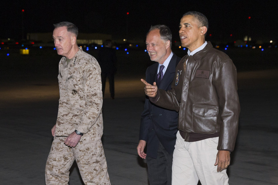 Photo - President Barack Obama, right, is greeted by US Ambassador to Afghanistan James Cunningham, center, and Marine General Joseph Dunford, commander of the US-led International Security Assistance Force (ISAF), as he arrives at Bagram Air Field for an unannounced visit, on Sunday, May 25, 2014, north of Kabul, Afghanistan. (AP Photo/ Evan Vucci)