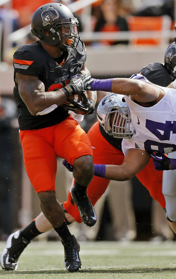 Kansas State's Ryan Mueller (44) tries to stop Oklahoma State's Jeremy Smith (31) on a carry in the first quarter during a college football game between the Oklahoma State University Cowboys (OSU) and the Kansas State University Wildcats (KSU) at Boone Pickens Stadium in Stillwater, Okla., Saturday, Oct. 5, 2013. Photo by Nate Billings, The Oklahoman