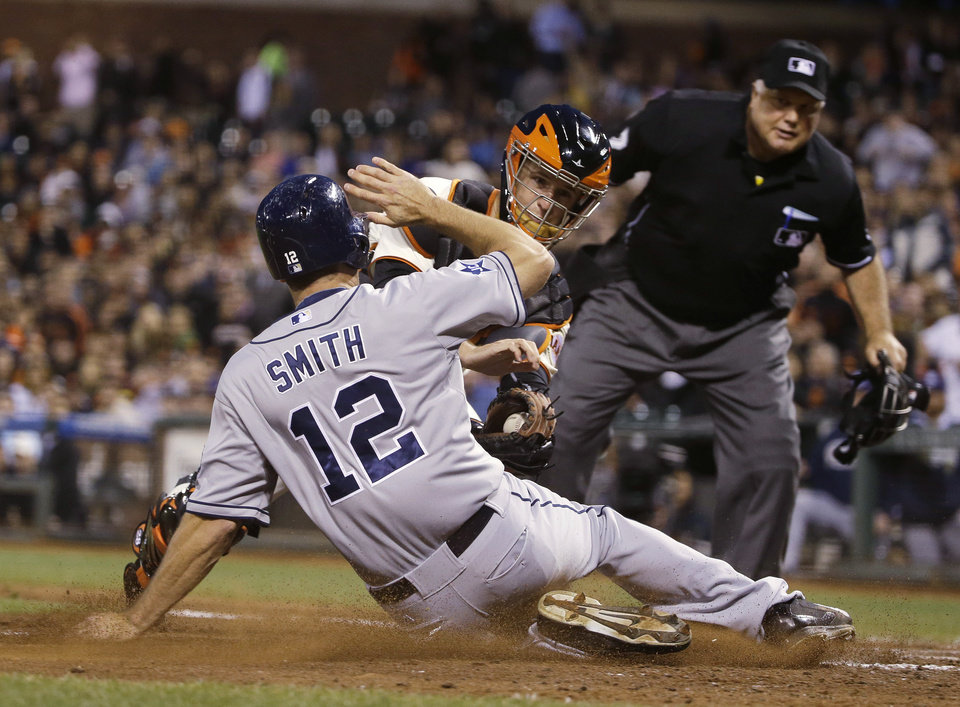 Photo - San Diego Padres' Seth Smith is tagged out at home plate by San Francisco Giants catcher Buster Posey as home plate umpire Brian O'Nora watches during the sixth inning of a baseball game Tuesday, June 24, 2014, in San Francisco. Smith tried to score from second on a single by Yasmani Grandal to center. (AP Photo/Eric Risberg)