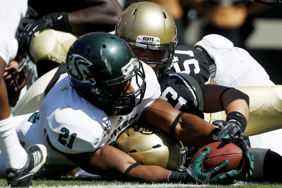 Photo -   Sacramento State running back A.J. Ellis, front, stretches to score a touchdown as Colorado defensive back Parker Orms, center, and defensive lineman Justin Solis cover in the first quarter of an NCAA college football game in Boulder, Colo., Saturday, Sept. 8, 2012. (AP Photo/David Zalubowski)