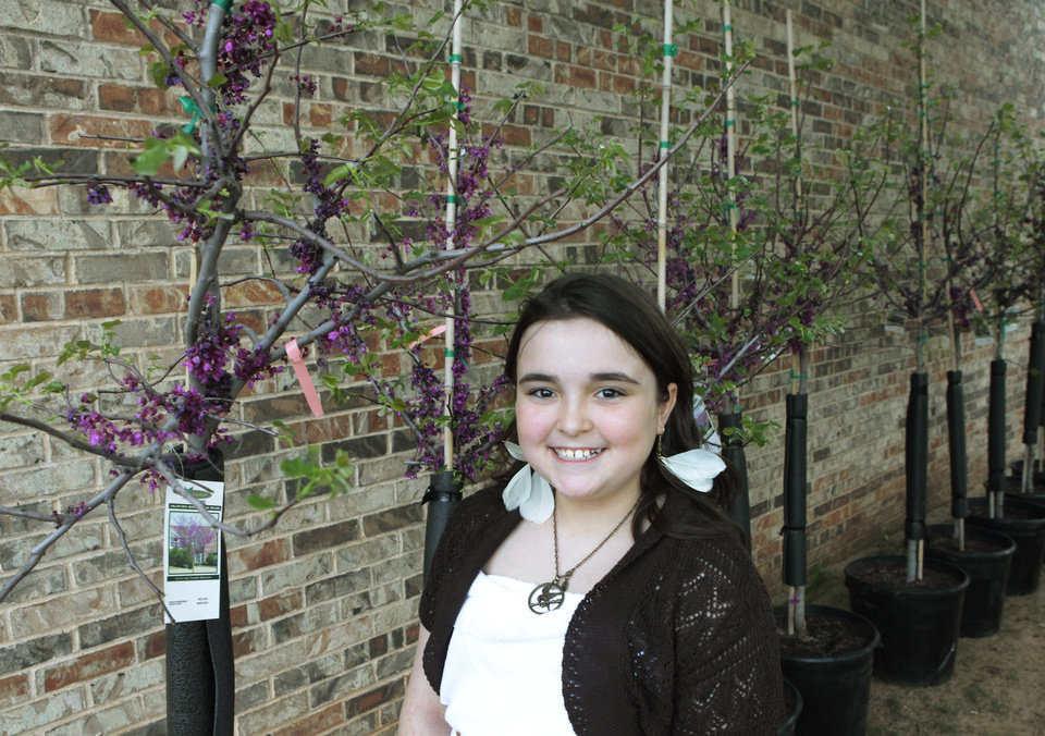 Northern Hills fifth-grader Riley McCue poses with her tree she won for her first place-winning art at Edmond's celebration of Arbor Week at the Edmond Library, March 26, 2012.  Photo By David McDaniel/The Oklahoman