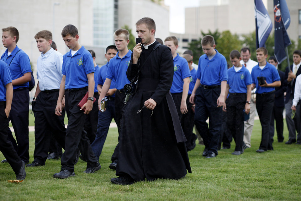 Photo - Father John Bourbeau, of St. Marys Kansas, leads a rosary procession in downtown Oklahoma City in protest of the Black Mass, Sunday, Sept. 21, 2014.  Photo by Garett Fisbeck, For The Oklahoman