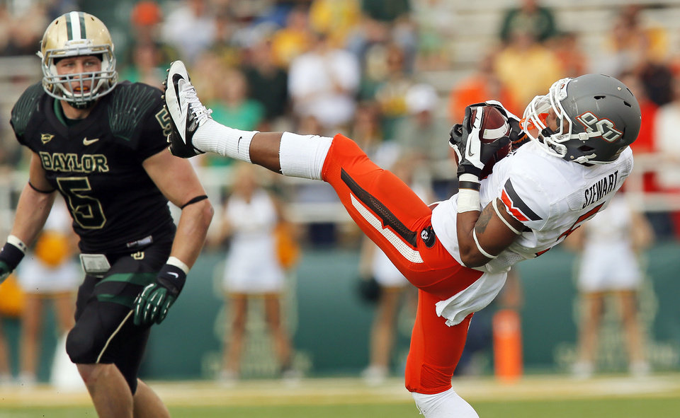 Photo - Oklahoma State's Josh Stewart (5) makes a catch as Baylor's Eddie Lackey (5) looks on during a college football game between the Oklahoma State University Cowboys (OSU) and the Baylor University Bears at Floyd Casey Stadium in Waco, Texas, Saturday, Dec. 1, 2012. Photo by Nate Billings, The Oklahoman