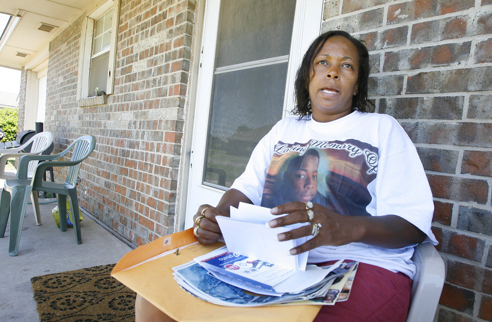 Photo - Sheila Osborn, Antwun Parker's aunt, looking through photos while on her sister's front porch talking about Parker in Oklahoma City Friday, May 29, 2009. Parker, 16, was killed by pharmacist Jerome Jay Ersland during an attempted robbery of Reliable Discount Pharmacy, 5900 S Pennsylvania Ave, on May 19, 2009.Photo by Paul B. Southerland, The Oklahoman