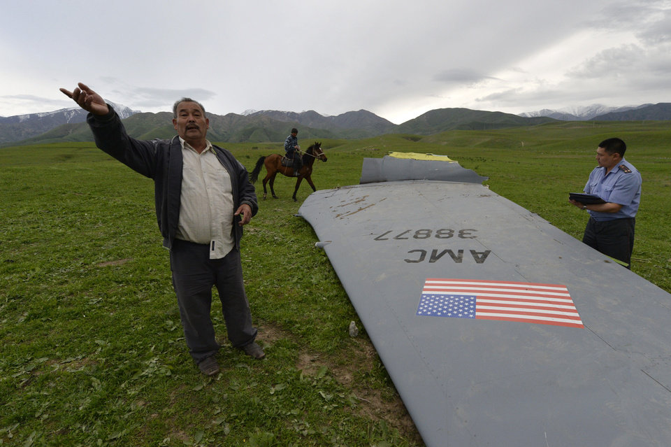 Photo - A Kyrgyz policeman investigates a U.S. Air Force KC-135 tanker aircraft wreckage as a local citizen speaks to The Associated Press photographer on a field near the village of Chaldovar, about 100 miles (160 kms) west of the Kyrgyz capital Bishkek, Friday, May 3, 2013. The emergencies ministry in Kyrgyzstan says a US military plane has crashed in the country. Kyrgyzstan hosts a US base that is used for troops transiting into and out of Afghanistan and for C-135 tanker planes that refuel warplanes in flight. (AP Photo/Vladimir Voronin)