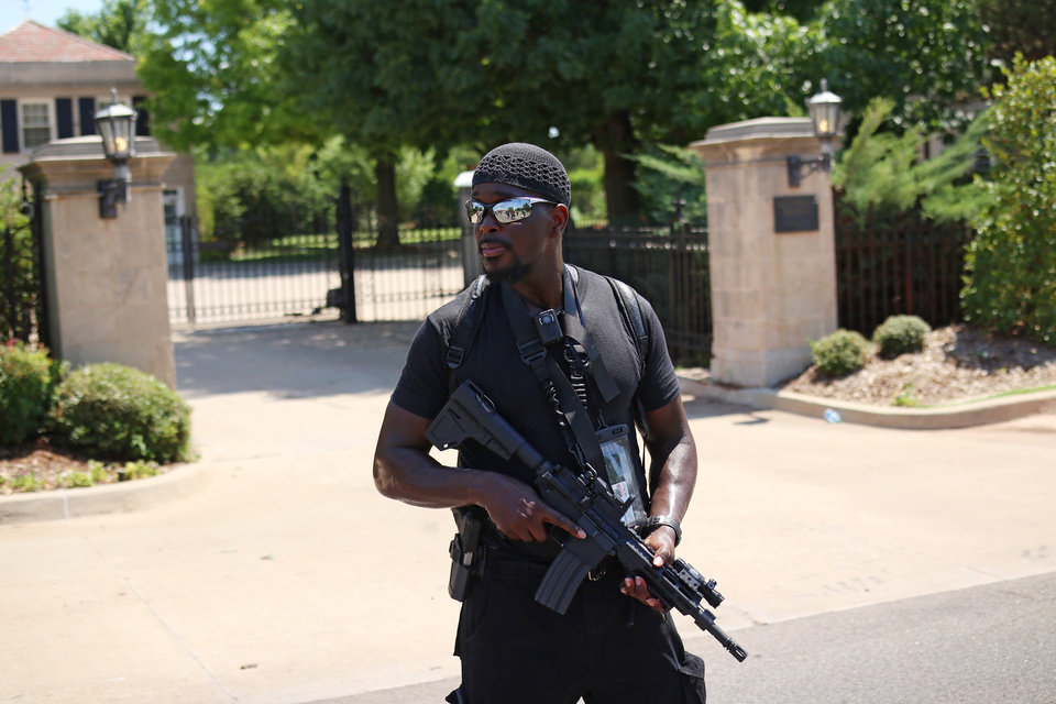 Photo - Omar Chatman stands in front of the gate to the Governor's Mansion at a 1,000 brothers and sisters in arms for second amendment walk by predominantly black men and women to advocate for their second amendment rights, Saturday, June 20, 2020. [Doug Hoke/The Oklahoman]