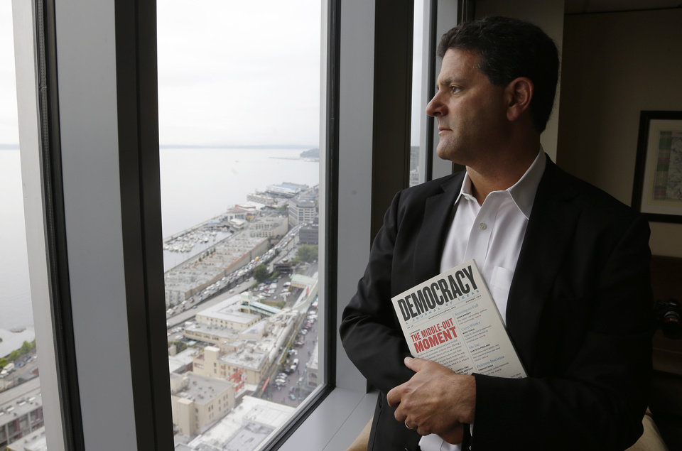 Photo - In this Aug. 2, 2013 photo, Venture capitalist Nick Hanauer poses for a photo by the window of his office in downtown Seattle. Washington state already has the nation's highest state minimum wage at $9.19 an hour, and Hanauer endorses calls to raise it, because he feels putting money in the hands of regular consumers could reduce the drop in demand for goods that he says has hurst our economy.  Hanauer is holding a copy of