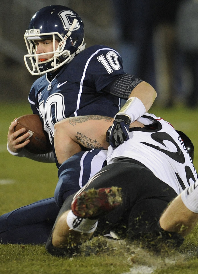 Photo - Connecticut quarterback Chandler Whitmer (10), left, is sacked by Cincinnati defensive lineman Dan Giordano (99), right, during the first half of an NCAA college football game at Rentschler Field in East Hartford, Conn., Saturday, Dec. 1, 2012. (AP Photo/Jessica Hill)