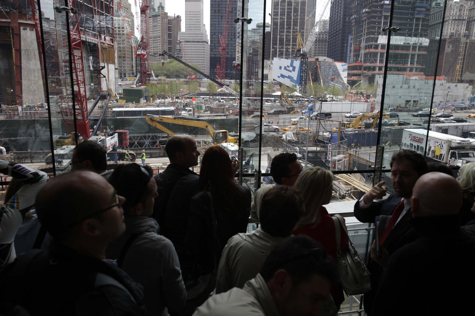 Photo - A crowd of people look over ground zero in New York, Monday, May 2, 2011.  Osama bin Laden, the face of global terrorism and architect of the Sept. 11, 2001, attacks, was killed in a firefight with elite American forces in Pakistan on Monday, May 2, 2011 then quickly buried at sea. (AP Photo/Seth Wenig) ORG XMIT: NYSW104