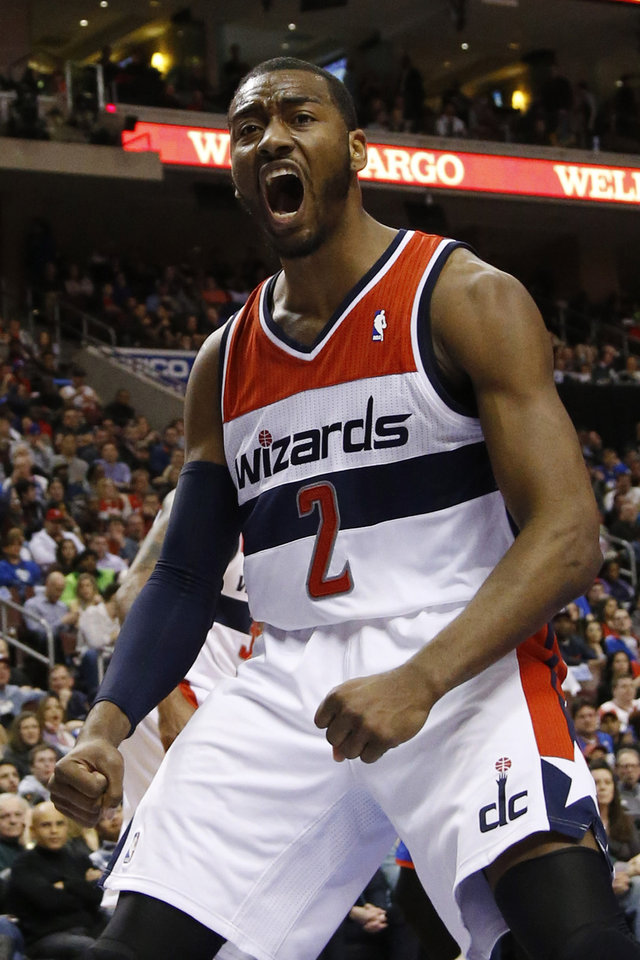 Photo - Washington Wizards' John Wall reacts after his dunk during the first half of an NBA basketball game against the Philadelphia 76ers, Saturday, March 1, 2014, in Philadelphia. (AP Photo/Matt Slocum)
