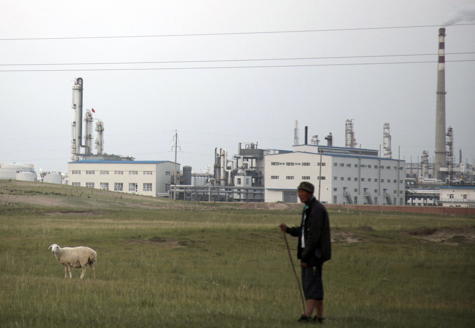 Photo - In this photo taken Wednesday, Aug. 6, 2014,  a sheep herder stands with a sheep outside a state-of-the-art power plant that turns millions of tons of coal every year into methane in northern China's Inner Mongolia province. Deep in the hilly grasslands of remote Inner Mongolia, twin smoke stacks rise more than 200 feet into the sky, their steam and sulfur billowing over herds of sheep and cattle. Both day and night, the rumble of this power plant echoes across the ancient steppe, and its acrid stench travels dozens of miles away. (AP Photo/Jack Chang)