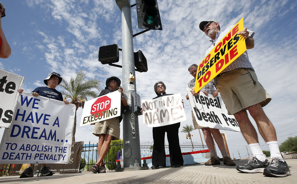 Photo - John Zemblidge, right, of Phoenix, leads a group of about a dozen death penalty opponents in prayer as they protest the possible execution of Joseph Rudolph Wood at the state prison in Florence, Ariz. on Wednesday, July 23, 2014. Arizona's highest court on Wednesday temporarily halted the execution of the condemned inmate so it could consider a last-minute appeal. The Arizona Supreme Court said it would consider whether he received inadequate legal representation at his sentencing. The appeal also challenges the secrecy of the lethal injection process and the drugs that are used. (AP Photo)
