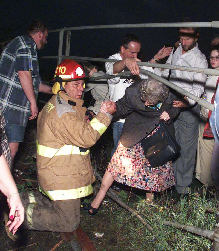 May 3, 1999 Oklahoma City Tornado:   Tornado damage, victims: A fireman helps an auditorium full of Westmoore patrons and south side residents through a fence near Westmoore High School.  Staff photo by Steve Sisney