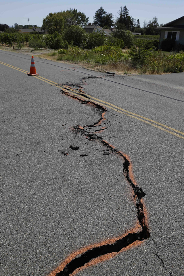 Photo - A cracked section of roadway is shown in the Carneros district following an earthquake Sunday, Aug. 24, 2014, in Napa, Calif.  The largest earthquake to hit the San Francisco Bay Area in 25 years struck before dawn on Sunday, sending scores of people to hospitals, igniting fires, damaging historic buildings and knocking out power to thousands of homes and businesses in California's wine country. (AP Photo/Eric Risberg)