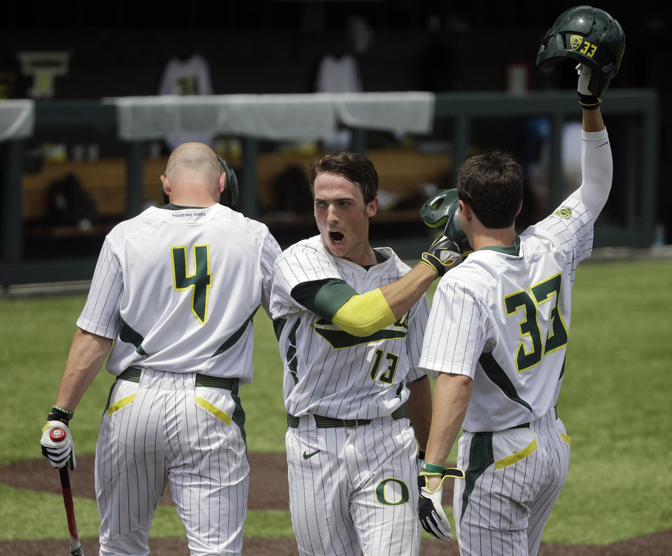 Photo - Oregon outfielder Tyler Baumgartner (13) celebrates with Kyle Garlick (4) and A.J. Balta (33) after Baumgartner hit a solo home run against Clemson during the fourth inning of an NCAA college baseball regional tournament game Friday, May 30, 2014, in Nashville, Tenn. (AP Photo/Mark Humphrey)