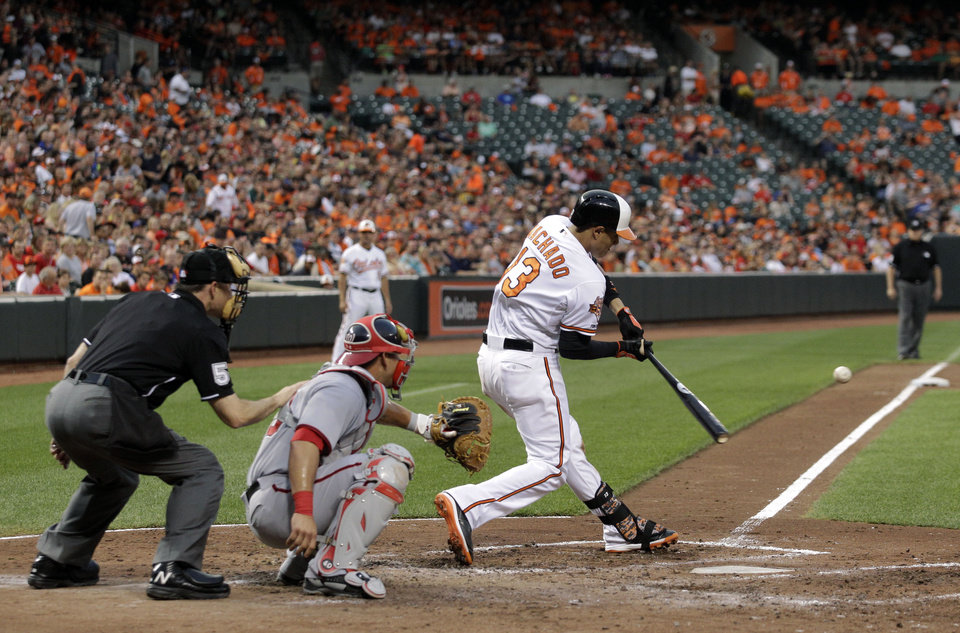 Photo - Baltimore Orioles' Manny Machado hits a solo home run in front of Washington Nationals catcher Wilson Ramos and home plate umpire Dan Iassogna in the fourth inning of an interleague baseball game, Wednesday, July 9, 2014, in Baltimore. (AP Photo/Patrick Semansky)