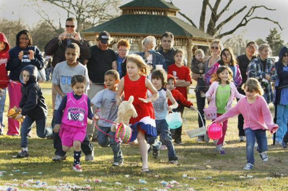 Photo - Children race to find eggs at the 2010 Easter egg hunt in Andrews Park in Norman. This year's hunt was scheduled for last week, but was rescheduled due to poor weather. The hunt is now scheduled for Friday.  OKLAHOMAN ARCHIVE PHOTO BY STEVE SISNEY  STEVE SISNEY