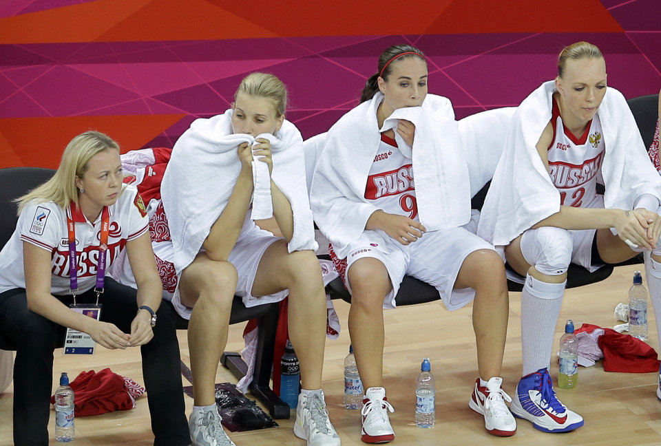 Photo - From left, Russia's Irina Osipova, Becky Hammon and Natalya Vieru sit on the bench during a women's basketball semifinal game at the 2012 Summer Olympics, Thursday, Aug. 9, 2012, in London. (AP Photo/Victor R. Caivano)