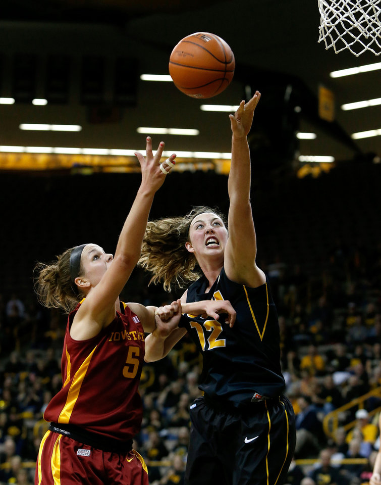 Photo - Iowa center Morgan Johnson (12) puts up ascot against Iowa State  forward Hallie Christofferson (5) during the first half an NCAA college basketball game Thursday, Dec. 6, 2012 at Carver-Hawkeye Arena in Iowa City, Iowa.  (AP Photo/The Gazette,Brian Ray)