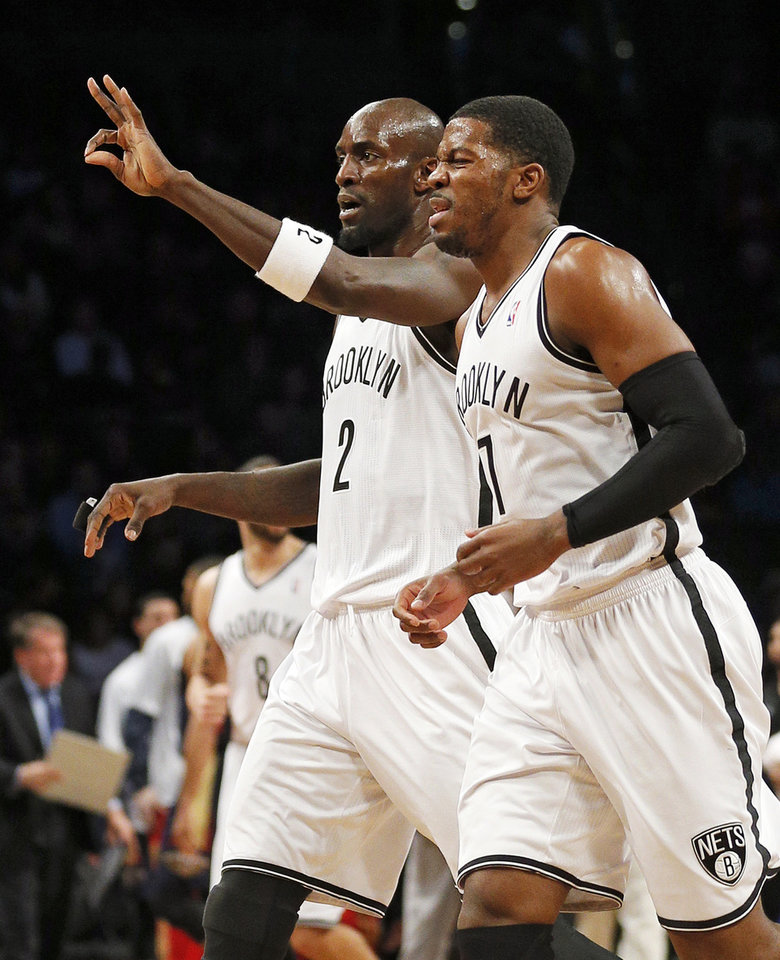 Photo - Brooklyn Nets forward Kevin Garnett (2) signals his three pointer as teammate Joe Johnson (7) runs with him in the first quarter of an NBA basketball game against the New Orleans Pelicans on Sunday, Feb. 9, 2014, in New York. (AP Photo/Paul J. Bereswill)