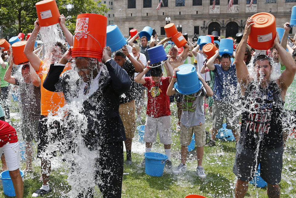 Photo - Boston City Councillor Tito Jackson, left in suit, leads some 200 people in the ice bucket challenge at Boston's Copley Square, Thursday, Aug. 7, 2014 to raise funds and awareness for ALS.The idea is easy: Take a bucket of ice water, dump it over your head, video it and post it on social media. Then challenge your friends, strangers, even celebrities to do the same within 24 hours or pay up for charity. (AP Photo/Elise Amendola)