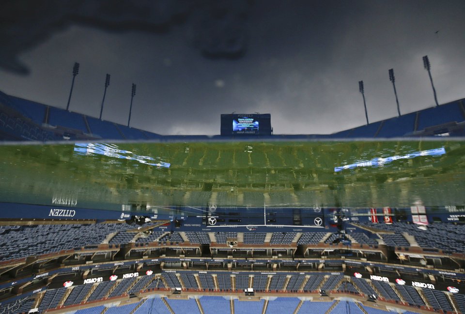 Photo -   The tennis court at Arthur Ashe stadium is shown as rain falls before play is to resume at the 2012 US Open tennis tournament, Saturday, Sept. 8, 2012, in New York. (AP Photo/Charles Krupa)
