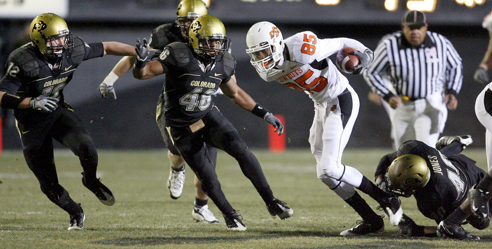 Photo - OSU's Damion Davis runs past Colorado's Patrick Mahnke, left, Anthony Perkins, and Brad Jones after a catch during the college football game between Oklahoma State University and the University of Colorado at Folsom Field in Boulder, Colo., Saturday, Nov. 15, 2008. BY BRYAN TERRY, THE OKLAHOMAN