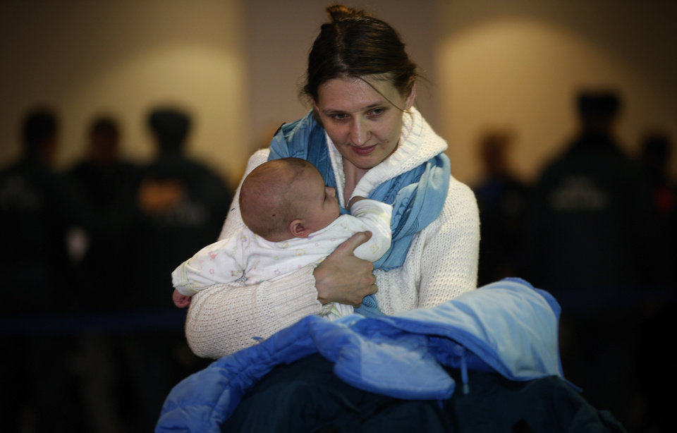 Photo - A Russian woman holds her baby while leaving passport control zone just after their arrival from Beirut in Moscow Domodedovo airport, Russia, Wednesday, Jan. 23, 2013. The Kremlin's evacuation of Russians from Syria on Tuesday marks a turning point in its view of the civil war, representing increasing doubts about Bashar Assad's hold on power and a sober understanding that it has to start rescue efforts before it becomes too late.The operation has been relatively small-scale - involving fewer than 100 people, mostly women and children - but it marks the beginning of what could soon turn into a risky and challenging operation.  (AP Photo/Alexander Zemlianichenko)