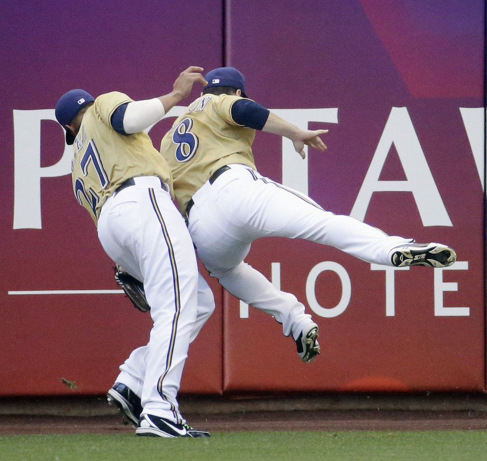 Photo - Milwaukee Brewers' Carlos Gomez and Ryan Braun (8) colide going after a ball hit by Philadelphia Phillies' Cameron Rupp during the sixth inning of a baseball game Thursday, July 10, 2014, in Milwaukee. Gomez caught the ball for the out. (AP Photo/Morry Gash)