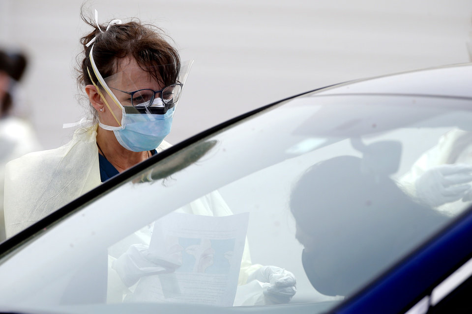 Photo - A Cleveland County Health Department employee talks with a person before collecting a sample at a COVID-19 drive-thru testing site at Griffin Community Park in Norman, Okla., Thursday, April 9, 2020. [Bryan Terry/The Oklahoman]
