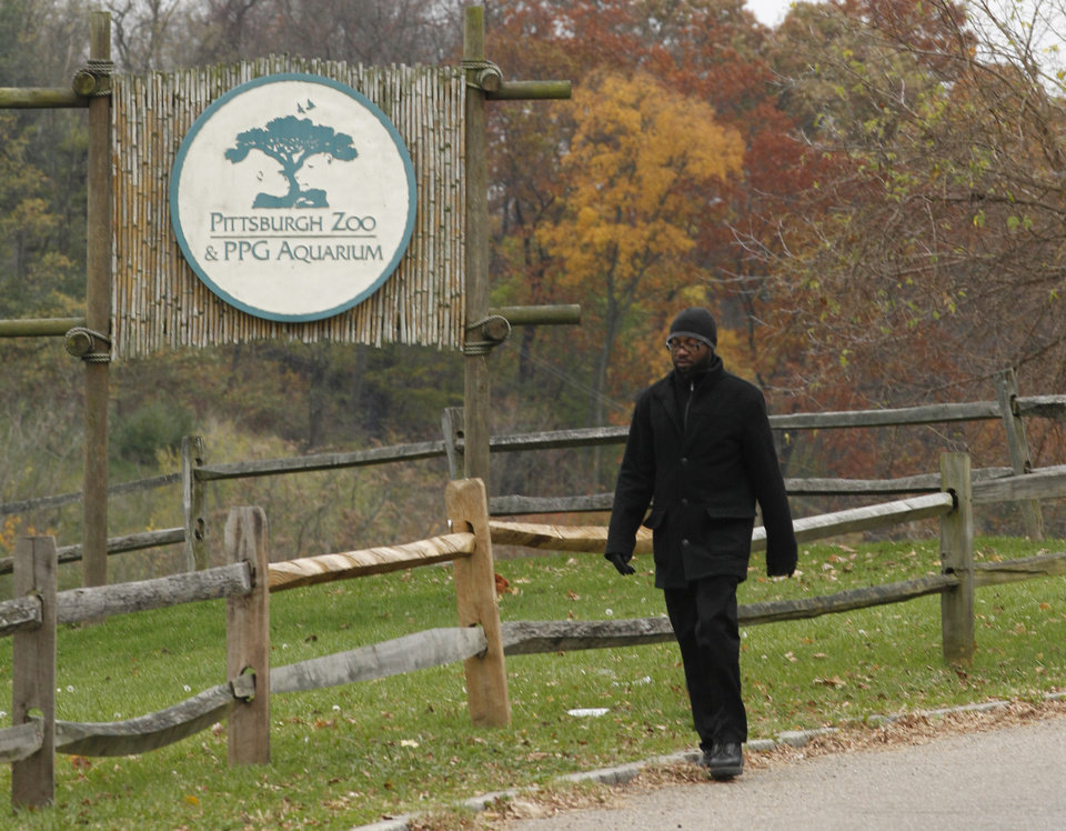 Photo -   A man walks by a sign near the entrance to the parking lots for the Pittsburgh Zoo and PPG Aquarium on Monday, Nov. 5, 2012, in Pittsburgh. Zoo officials said a young boy was killed after he fell into the exhibit that was home to a pack of African painted dogs, who pounced on the boy and mauled him on Sunday, Nov. 4, 2012. It's not yet clear whether the boy died from the fall or the attack, said Barbara Baker, president of the Pittsburgh Zoo & PPG Aquarium. (AP Photo/Keith Srakocic)