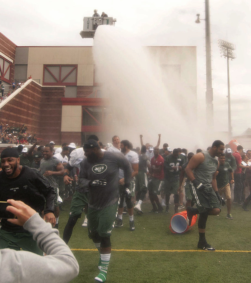 Photo - In this Aug. 13, 2014,  photo, New York Jets players and coaches react under a large spray of water as they celebrated the final day of NFL football training camp in Cortland, N.Y. The Jets got soaked for a good cause. The team accepted the New England Patriots' Ice Bucket Challenge to their AFC East rivals and ended its last public practice at SUNY Cortland  by getting doused _ with help from the Cortlandville Fire Department. (AP Photo/The Cortland Standard, Bob Ellis )
