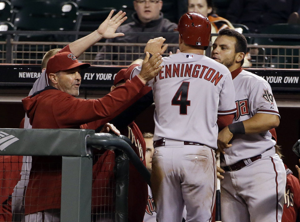 Photo - Arizona Diamondbacks' Cliff Pennington (4) is greeted in the dugout after scoring on a single from Tony Campana during the 10th inning of a baseball game on Thursday, April 10, 2014, in San Francisco. Arizona won 6-5. (AP Photo/Marcio Jose Sanchez)