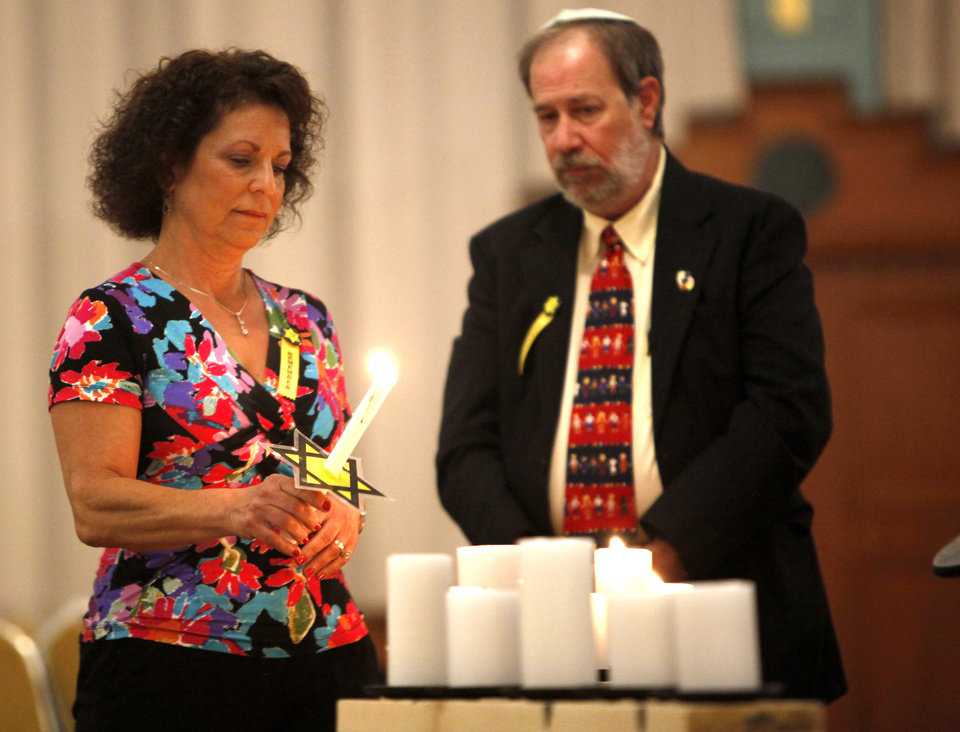 Photo - Frances Stewart lights a candle during the 21st annual Holocaust Commemoration service Tuesday at the Civic Center Music Hall in Oklahoma City.  SARAH PHIPPS - SARAH PHIPPS