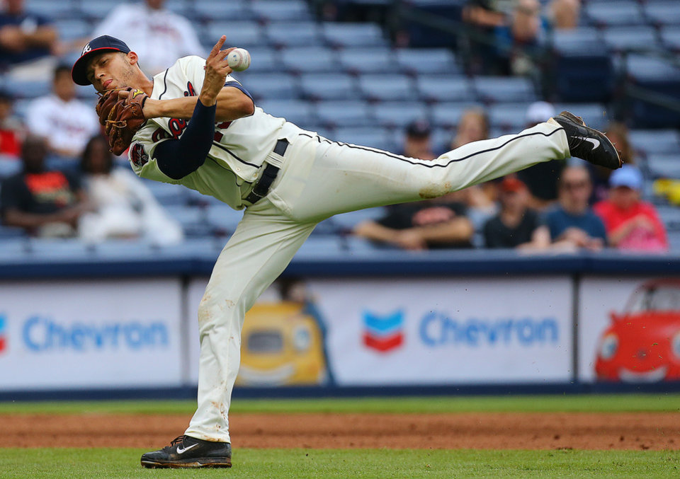 Photo - Atlanta Braves Andrelton Simmons makes a difficult play on a ground ball hit by Phillies Marlon Byrd who was able to reach first for a single  during the seventh inning of a baseball game on Sunday, July 20, 2014, in Atlanta.  (AP Photo/Atlanta Journal-Constitution, Curtis Compton)