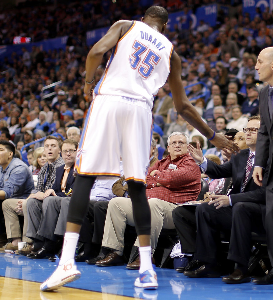 Photo - Oklahoma City's Kevin Durant (35) slaps hands with coach Scott Brooks after Brooks received a technical foul during an NBA basketball game between the Oklahoma City Thunder and the Golden State Warriors at Chesapeake Energy Arena in Oklahoma City, Friday, Jan. 17, 2014. Photo by Bryan Terry, The Oklahoman