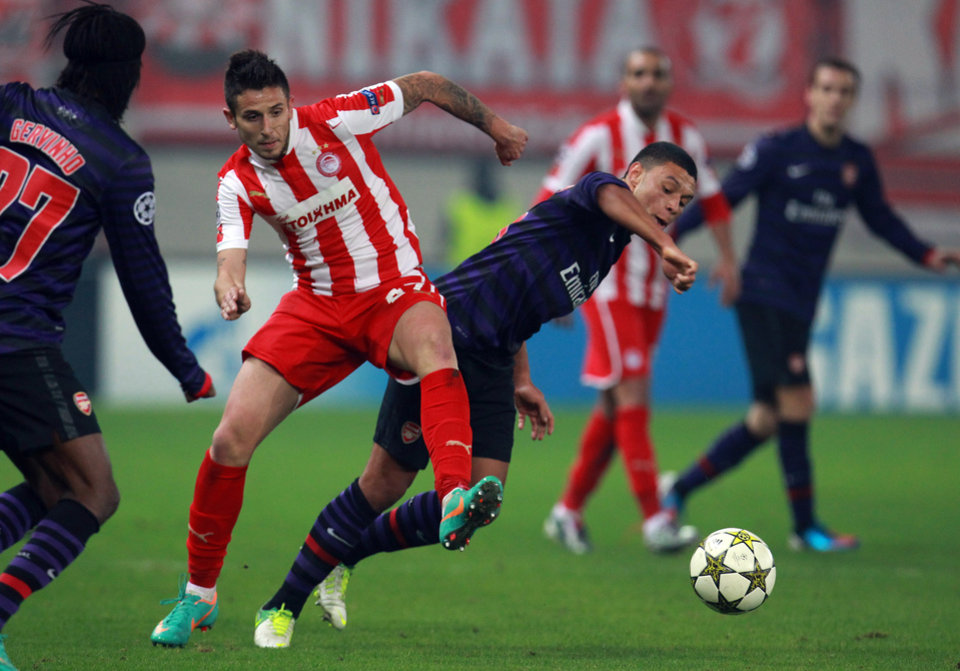 Olympiakos' Leandro Greco, left, fights for the ball with Arsenal's Alex Oxlade-Chamberlain during a group B Champions League soccer match in the port of Piraeus, near Athens, Tuesday, Dec. 4, 2012. (AP Photo/Thanassis Stavrakis)
